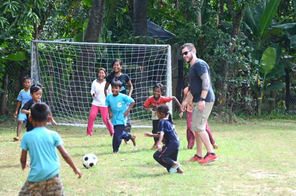 Chris playing soccer with the children